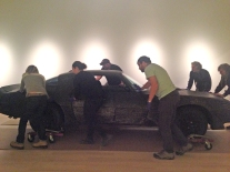 The team of preparators moves the car through AGH Gallery Level 1 to the exhibition space.